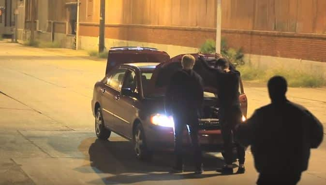 Sam (right) and Colby (left) check the car while a man creeps up behind them ready to kidnap Sam (Picture: Sam Pepper/YouTube)