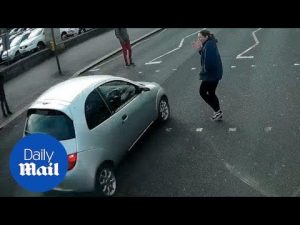 Car narrowly misses pedestrian when failing to stop at red light – Daily Mail