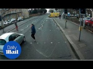 Car narrowly misses woman when failing to stop at red light – Daily Mail