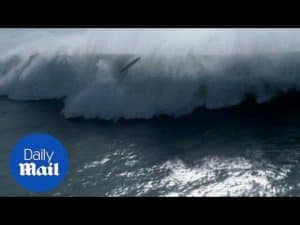 Moment surfer and jet ski are battered by enormous waves – Daily Mail