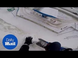 Snowboarder comes close to deathly fall and stops on cliff edge – Daily Mail