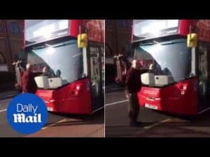 Stand-off as angry man refuses to move from in front of bus in Putney – Daily Mail
